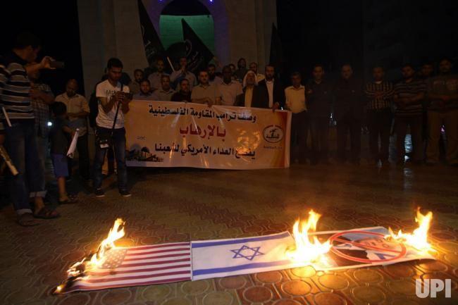 Palestinian demonstrators burn posters depicting a U.S. flag, an Israeli flag and Israeli Prime Minister Benjamin Netanyahu during a…