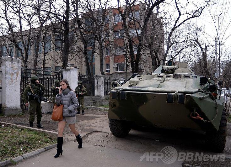 ロシアの「支配」進むクリミア、異議はささやき声のみに 国際ニュース:AFPBB News    ウクライナ南部クリミア半島のシンフェロポリ(Simferopol)の海軍本部前で、街頭を警備するロシア軍兵士の前を通り過ぎる女性(2014年3月18日撮影)。(c)AFP/Filippo MONTEFORTE