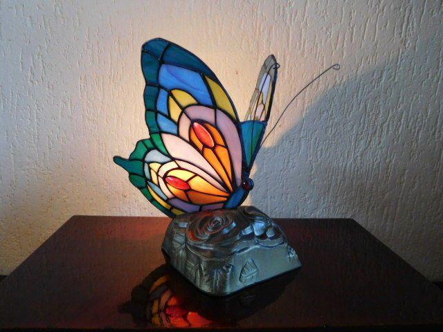In zeer goede staat verkerende Tiffany-style vlinderlamp. 's Avonds een feeriek sieraad in uw huis.  Foto's genomen bij schemering&daglicht zodat u uw mening op een juiste wijze kunt vormen.  Zie foto's.   Afmetingen: ca 23 cm hoog, spanwijdte ca 16cm  Gewicht: ca 1000 gram   Wordt aangetekend en zeer goed verpakt verzonden via Post NL Track Trace
