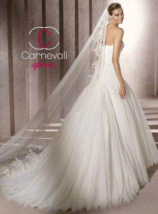 A strapless tulle A-Line gown with scalloped sweet heart neckline and detailed with Chantilly applique and beading. It features a beautiful beaded detail under the bust, a full pleated skirt accompanied by a chapel train.