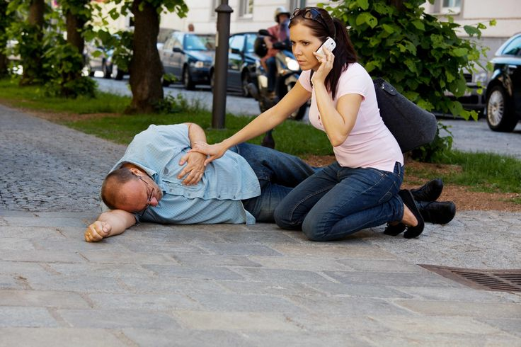 a man lying on the sidewalk holding his chest, having a heart attack or stroke, with a woman helping him and calling for help on the phone