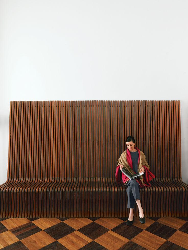 Here, Smith sits on a vintage rosewood bench designed by the Swiss-born British architect Richard Seifert.  Photo by: Chris Tubbs