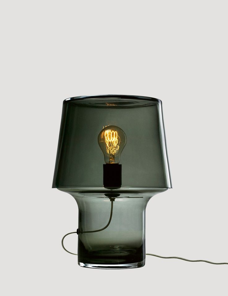 The COSY table lamp series focuses on the attractiveness of glass and the beauty of its changing reflections. Placing the light bulb at the centre of the design, the lamp is made with mouth-blown glass and comes with a textile chord. COSY can be used to add personality and atmosphere to any setting, whether on the table, shelf or floor.