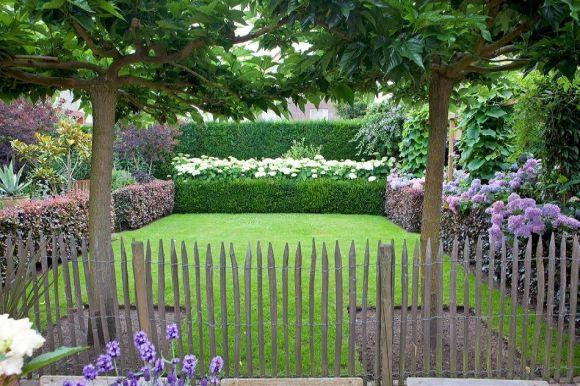 Het gazon wordt geflankeerd door hagen van rode beuk. Achterin groeit hortensia 'Annabelle', rechts staat de pergola.
