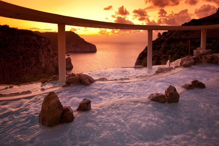 Hotel Hacienda Na Xamena (Ibiza)  Situado sobre un acantilado a más de 180 metros de altura, ofrece una piscina formada por cascadas suspendidas que quita los sentidos. Para nosotros no hay mejor plan que darse un baño en este spa mirando cómo el atardecer tiñe de naranja el Mediterráneo.