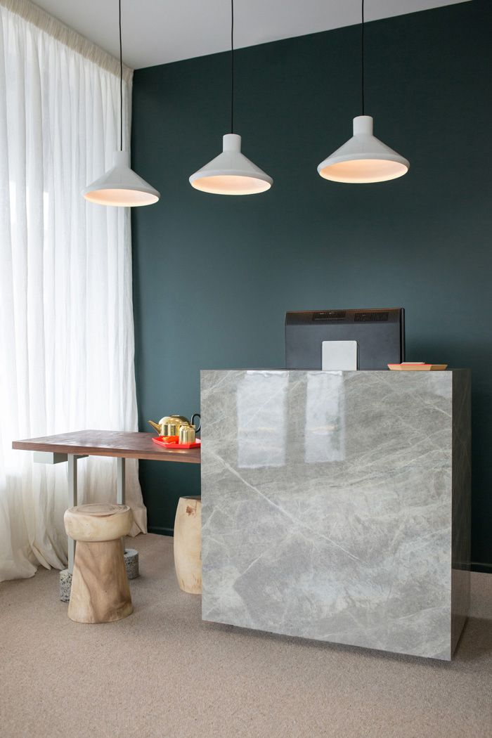 The natural colours and textures of the counter and nail bar sit against a deep green back wall with accents of coral | Haven (373 Dominion Road, Auckland) | Photo by the talented Jeremy Toth | Fit out by Material Creative.