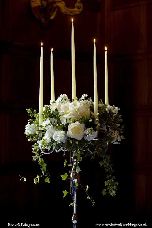 Silver candelabra with white roses, white stocks and white hydrangea by Exclusively Weddings. Photo by Kate Jackson