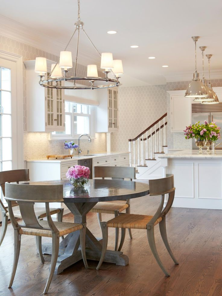 A zinc-topped round table is surrounded by wood and rattan klismos chairs, adding a contemporary touch to this transitional eat-in kitchen. A polished nickel chandelier illuminates the dining area and complements the pendant lighting over the island as well as the neutral walls and crisp white cabinetry.