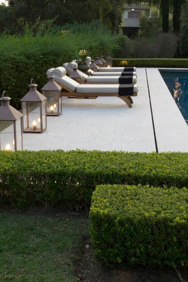 Smooth pale limestone terrace with elegant loungers and lanterns | clipped hedges