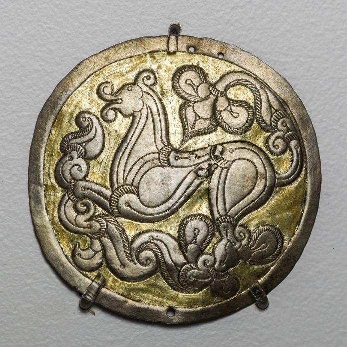 Hajfonatkorong a Balatonújlak-Erdő dűlőn feltárt 10. századi sírokból, Magyar Nemzeti Múzeum. Aranyozott ezüstlemezekből készült.Az ékszer előoldalán mitikus állatalakok láthatók, amelyek lábait és farkát növényi motívumokká formálta az ötvös. A finoman kidolgozott minta párhuzamai megtalálhatók a bizánci és a sztyeppei emlékek között.
