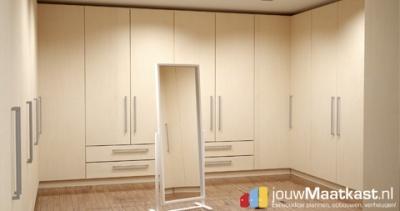 Luxe inloopkast met hoge doorlopende deuren. Helemaal op maat gemaakt en door de klant zelf te ontwerpen. Door de grote draaideuren en brede lade geeft het een rustige uitstraling.