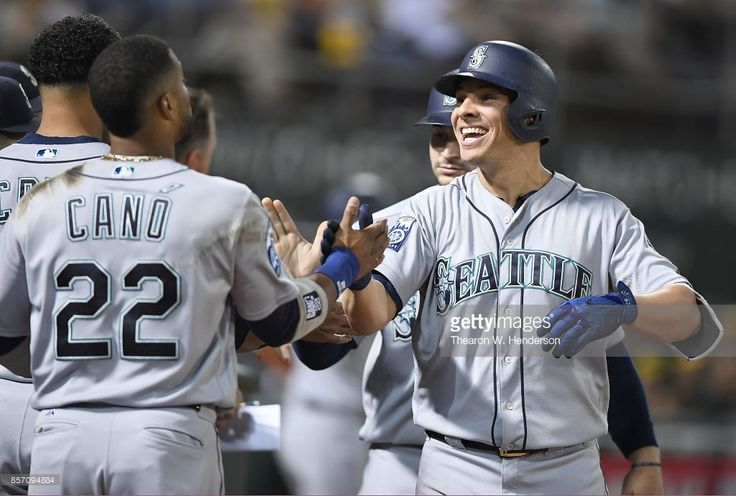 Danny Valencia #26 and Robinson Cano #22 of the Seattle Mariners celebrates after Valencia hit a three-run homer against the Oakland Athletics in the top of the seventh inning at Oakland Alameda Coliseum on September 26, 2017 in Oakland, California.