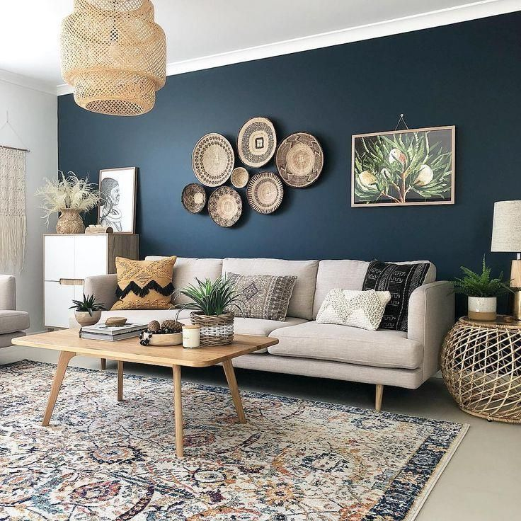 A Dark Blue Accent Wall With Cream Colored Sofa Wicker Basket