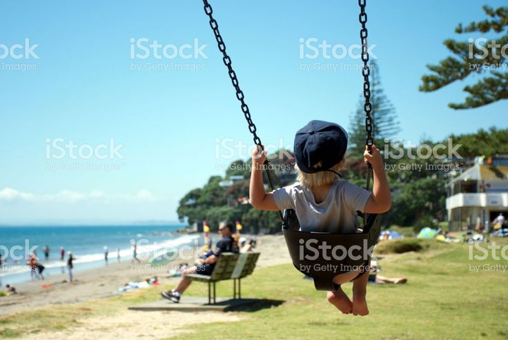 A Child swings on a Swing at a Beach Park in Summer royalty-free stock photo
