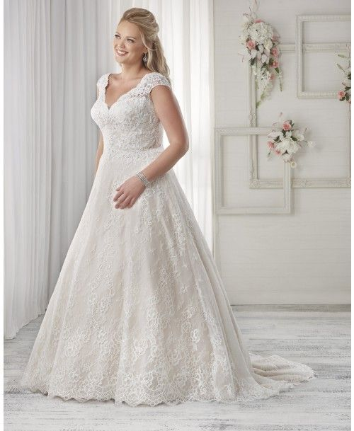 1601 - This lace adorned A-line wedding gown is traditional and romantic. The dual lace adds dimension and softness. The scalloped V neckline continues to create lovely cap sleeves.   View our entire plus size bridal collection on our website.