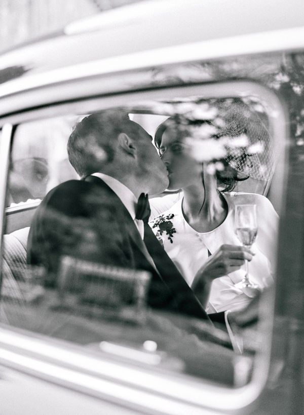 Bride and groom kissing in car. Photo: Katie Stoops