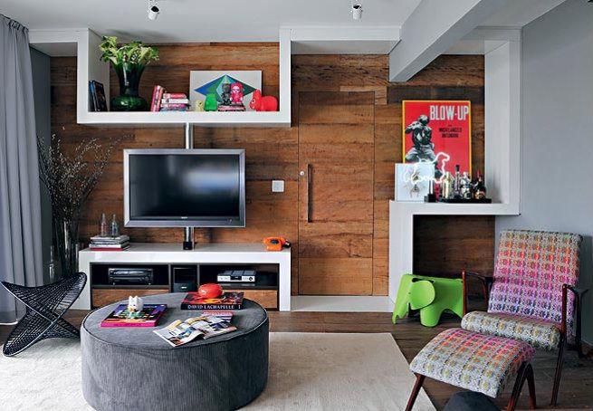 O espaço do home theater tem madeira canela de demolição sobre o piso e a parede em que fica a porta de entrada  Editora Globo / Casa e Jardim
