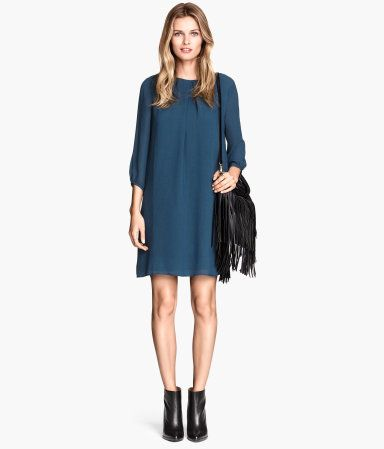 Dress in an airy, woven fabric with 3/4-length sleeves, decorative pleat at front, and visible zip at back of neck. Lined.