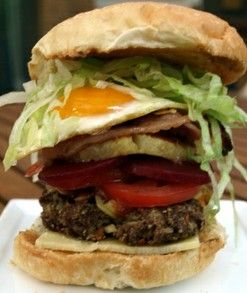 An Australian hamburger-with-the-lot contains a meat patty, fried onion, cheddar cheese, tomato, lettuce, fried egg, pineapple, pickled beetroot, bacon and a squirt of tangy barbeque or tomato sauce (ketchup). Nothing more, nothing less.