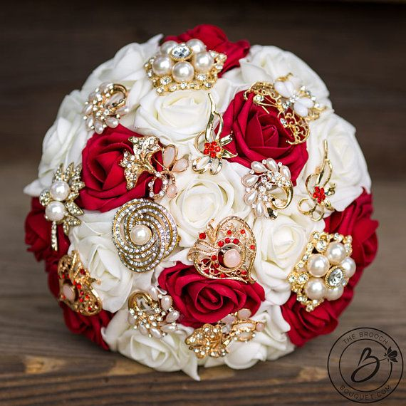 """""""Indian Gems"""" Deep Red Brooch Wedding Bouquet With Red Roses And Silver Brooches  This one is a stunner! Very popular color combination, especially in Indian weddings! Beautiful bold red against cream is the perfect background for the sparkly gold plated brooches! Made with our signature Soft Touch roses in deep red and ivory colors and variety of small brooches. Bottom is lined with satin ribbon and matches the handle ribbon. Handle is wrapped in gold and can be decorated for the perfect…"""
