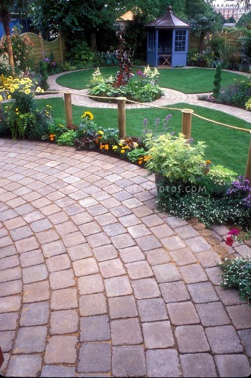 Brick pavered circular patio overlooking backyard with gazebo and garden beds and walkway