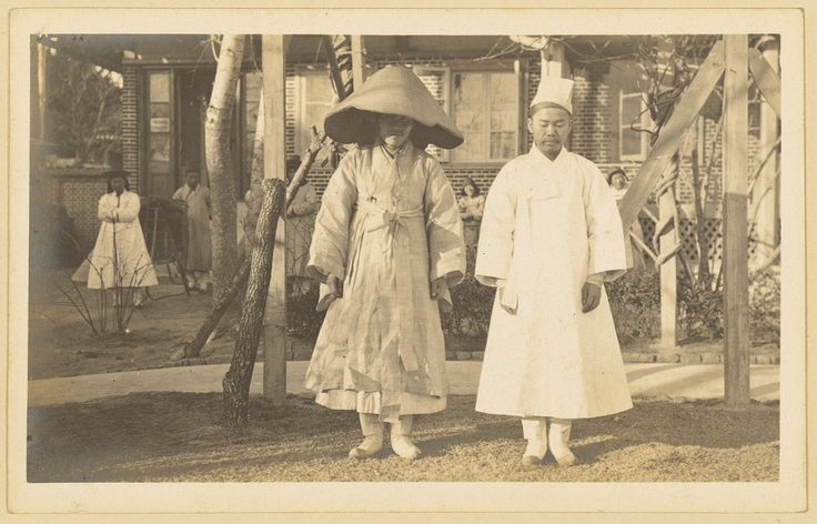 [2 Koreans in their mourning dress] 1904. When mourners went outdoors, they wore a long coat over their mourning dress. The coat sleeves differed in width according to social class: wider sleeves for upper classes and narrower sleeves for lower classes. All mourners wore conical hats made of finely-cut bamboos on the outside and of sedge on the inside.e They carried a 'poson' (fan made from hemp cloth) in order to cover their faces.