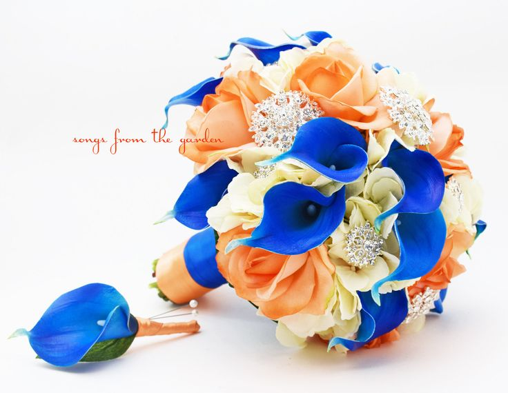 Glamorous rhinestones and brooches with royal blue, orange and ivory blooms are a gorgeous pairing in this lush and lovely silk flower bridal bouquet with matching groom's boutonniere. This bouquet ca