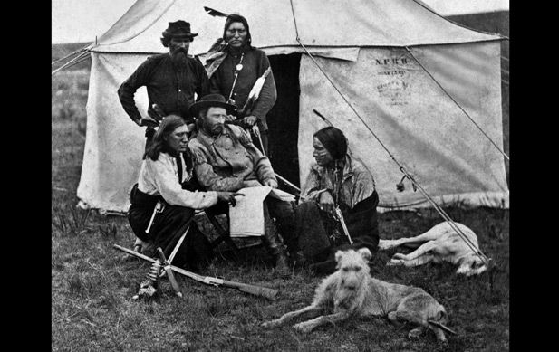 A rare print made in the early 1870's in Montana territory, showing General George A. Custer and some of his scouts. The Indian standing by the tent door is thought to be Curly, one of the scouts mentioned early in IN A RENEGADE'S EMBRACE.