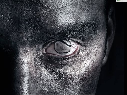 A mixture of dark and light tones across the mans face. Lightest around the eye and darker towards the outwards of his head and background. Harsh dramatic tone is used and is quite defined.