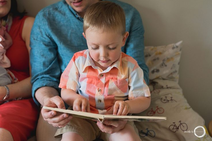 Boy reading on Dad's lap during in home newborn lifestyle photo session in Ottawa.