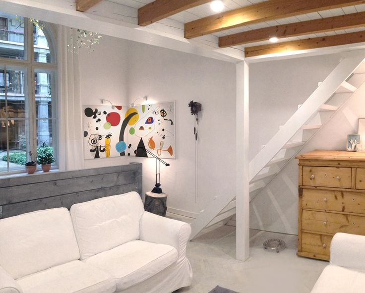 Tiny contemporary split-level studio apartment in Budapest featuring loads of white, wooden furniture, black wires and a bit of glass.