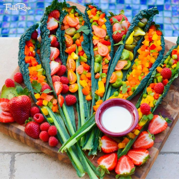 FullyRaw   -    FullyRaw kale tacos with a light lemon tahini sauce! Rainbow bell peppers, tomatoes, raspberries, strawberries, carrots, and mango diced and fit into dinosaur kale leaves! Let your dinners be magical!  Kristina Carrillo-Bucaram Rawfully Organic Co-op www.instagram.com/fullyrawkristina