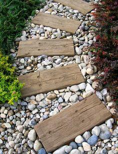 Weg im Garten - Balken aus Treibholz dienen als Trittplatten und sind mit Kies umrahmt