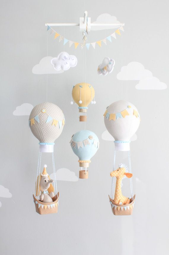 The most adorable hot air balloon baby mobile with a baby giraffe and elephant floating in their boats. A whimsical baby mobile for your travel