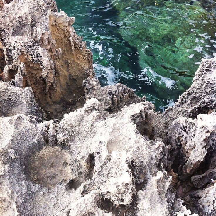 Ancient seabed rocks and emerald crystal water on the path of Capo Caccia