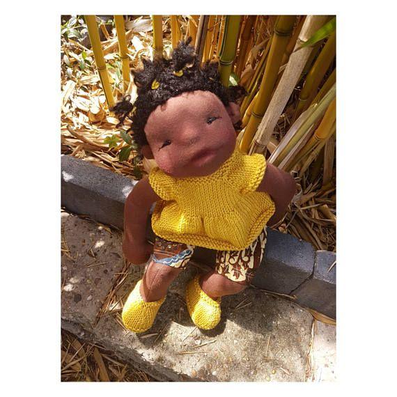 Dit is Saffran. Zij is gemaakt van NH donkerbruine tricot en stevig gevuld met schone gekaarde schapenwol. Ze is de grotere versie (45 cm) van de babypop. Hett lijfje heeft details als knieën, een navel, billen en oortjes Haar gezichtje is gedetailleerd vormgegeven met naaldvilt technieken en heeft blosjes van rode bijenwas op wangen, neus en mond. Haar ogen zijn zwart geborduurd. Haar haar is van Dolly-Mo loop mohair gehaakt. De staartjes zijn met gele elastiekjes vastgezet. Haar garderobe…