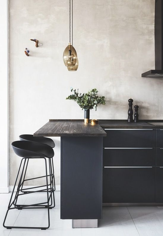 Elegant kitchen design with a rustic wooden tabletop and black cabinets with metal handles. We love the golden details.