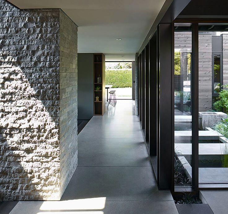 Before the renovation, the courtyard was visible mainly from the living room. Now, the house's main hallway borders the courtyard. Though the courtyard is fully enclosed, the design team visually brought it indoors by planting a small patch of black mondo grass inside, in line with a strip of the same grass planted outdoors.
