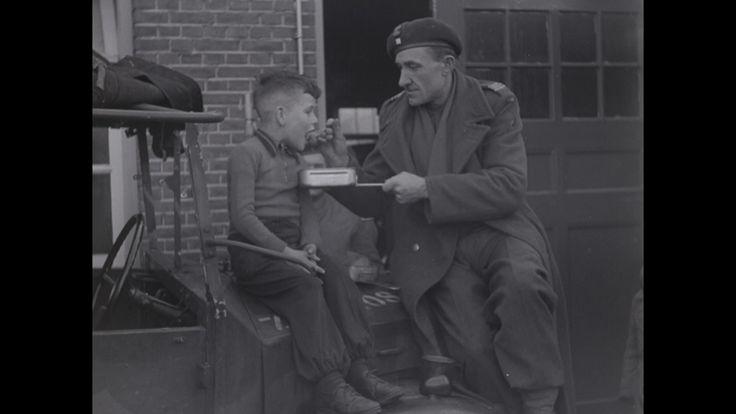 """Video: VOEDSELFILM BREDA, BEVRIJDING BREDA (1944) - vervalste persoonsbewijzen maken. Ze beramen een overval op Breda in de dagen na de bevrijding. Lege winkels, voedsel alleen te krijgen via de voedseldistributie. Op deuren geschilderde """"oranje"""" leuzen.  Overal hangen foto's van de Koningin. Rijen wachtende mensen bij winkels en bij het distributiekantoor waar ambtenaren distributiestamkaarten uitdelen. Huisvrouw met boodschappentas verlaat winkel en gaat naar huis. Ze pakt boodschappentas…"""