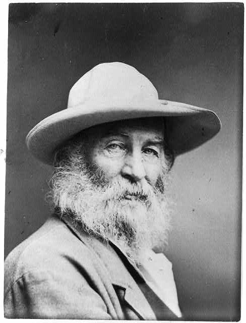 Walt Whitman, head-and-shoulders portrait, facing front, wearing hat
