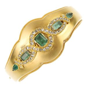 A late 19th century gold emerald and diamond bangle