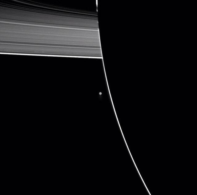 Enceladus moon orbiting Saturn