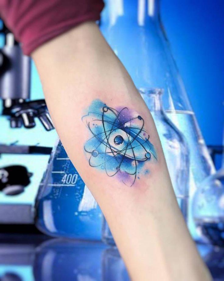 Tatuaje de un átomo de estilo acuarela, situado en el interior del antebrazo.