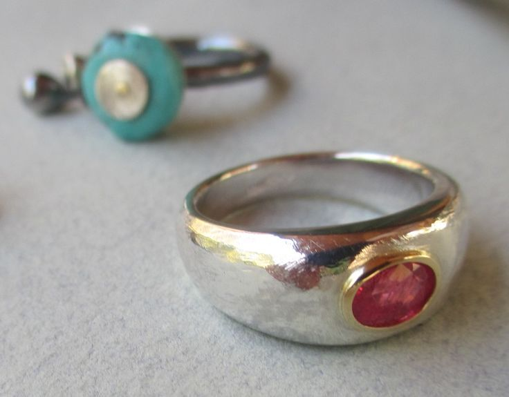 Men's textured Ruby Ring commission turquoise pebble ring in background