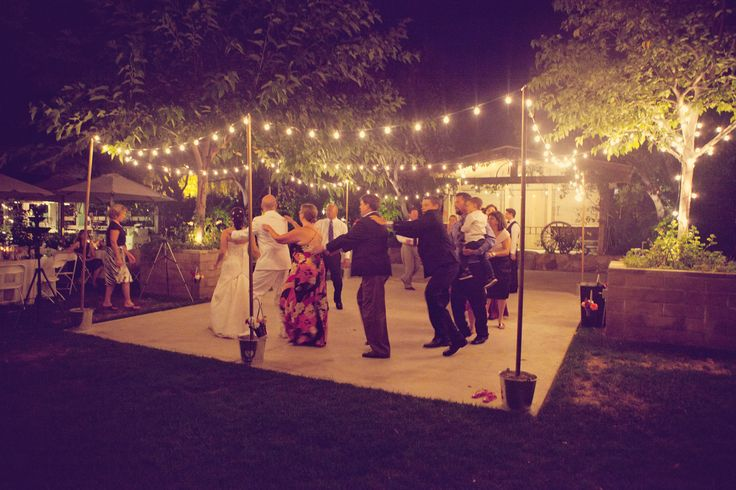 Wedding Dance Floor:  Dianna wanted the dance area to be brighter, so Tony made these poles on which to string more lights.  He cut two wooden disks with holes in the center to keep the poles upright.  Then, he filled the buckets with gravel to weigh them down.