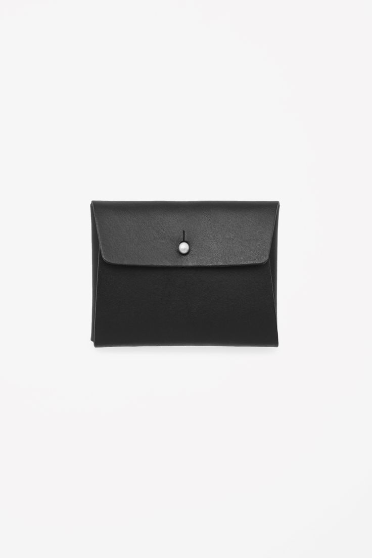 This cardholder is made from raw-cut unlined leather that folds in on itself to be secured with a press stud fastening.