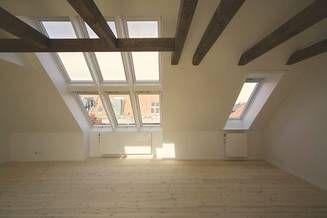 Et stort sammenbygget vinduesparti giver masser af dagslys i et højloftet rum med fritlagt tagkonstruktion.