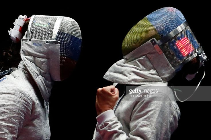 Ukraine's Olena Kravatska (R) reacts next to Russia's Sofya Velikaya during the womens team sabre gold medal bout between Russia and Ukraine as part of the fencing event of the Rio 2016 Olympic Games, on August 13, 2016, at the Carioca Arena 3, in Rio de Janeiro. / AFP / Thomas COEX