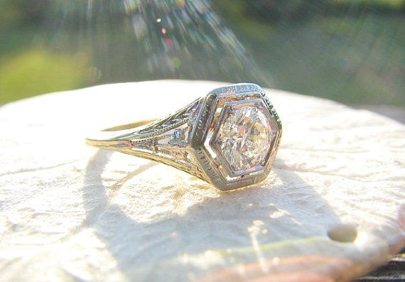 This elegant antique engagement ring dates from the Edwardian to very early Art Deco period....the lovely flower blossoms and filigree details enhance