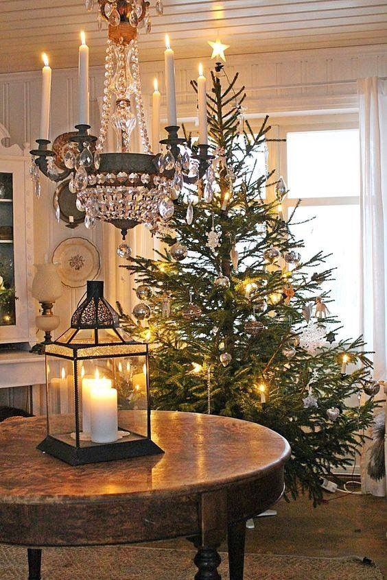 Elegant Christmas decor with crystal chandelier, lantern with candles on vintage table, and fresh Christmas tree. #SwedishChristmas #christmasdecor #vintageChristmas VIBEKE DESIGN